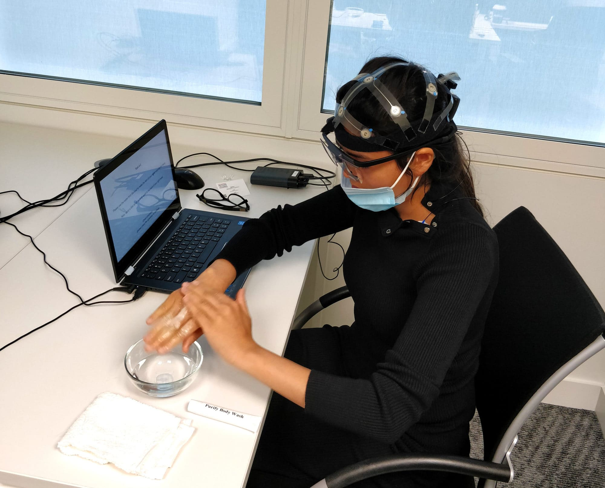 A woman with EEG equipment working on a computer.