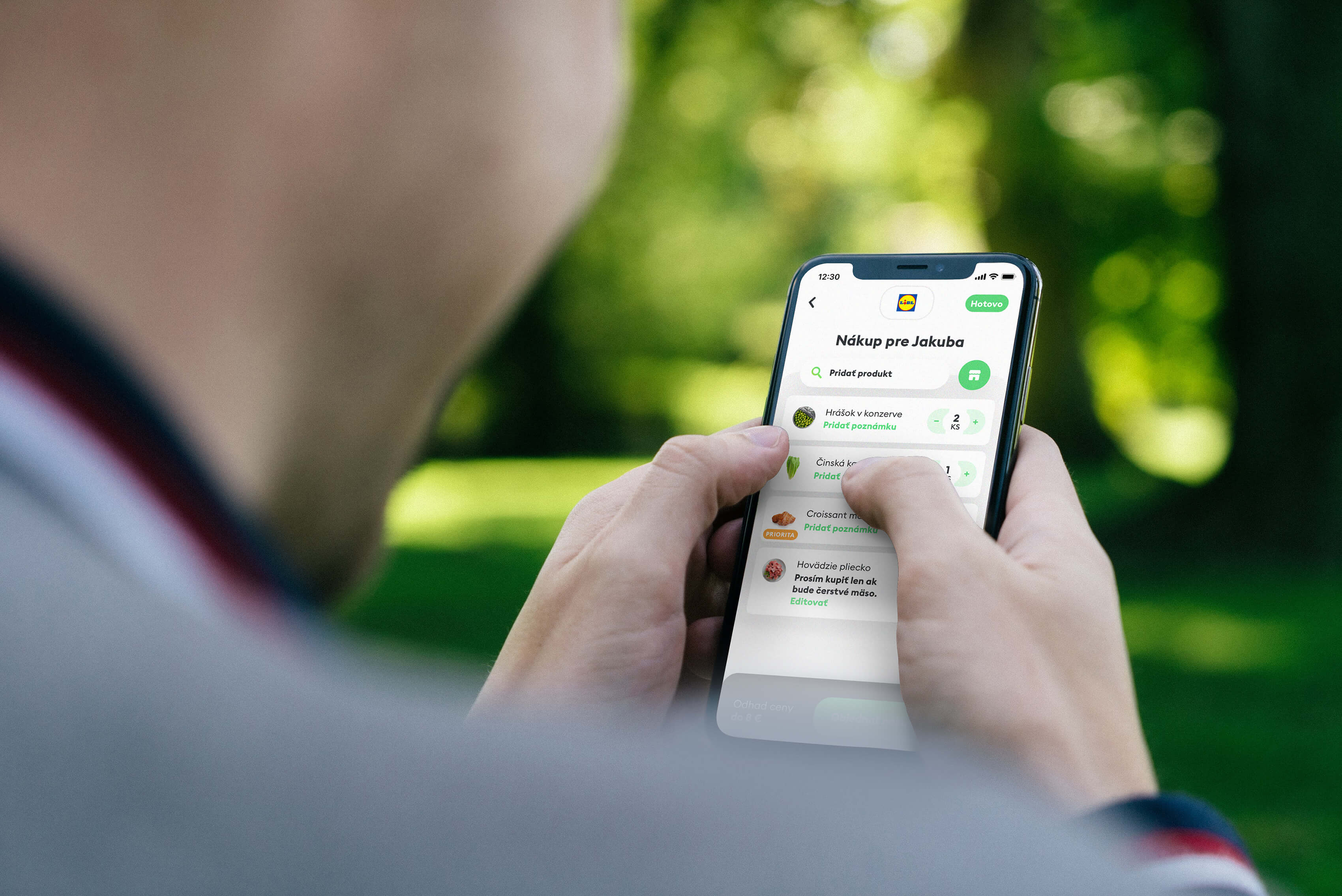Muž držící mobilní telefon s aplikací na objednání potravin.