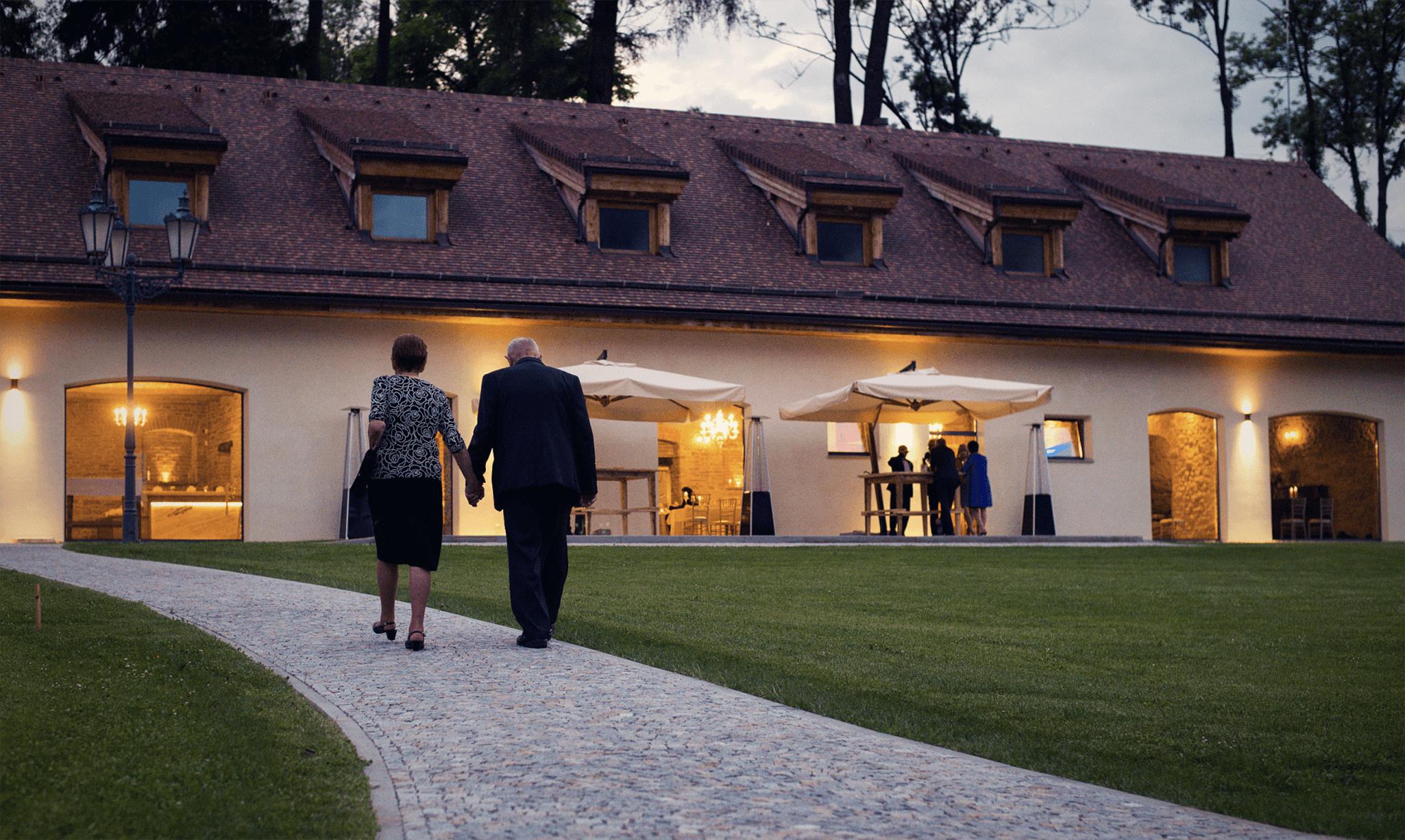 Starší lidé jdou směrem ke krásné budově v podvečer.