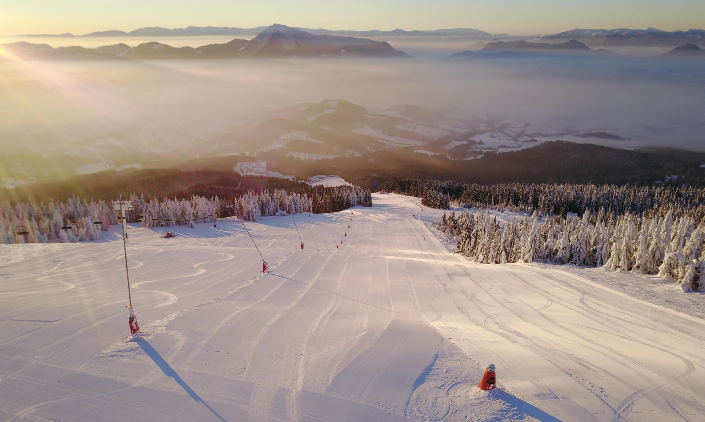 Pohled na sjezdovku a slovenské kopce při východu slunce.
