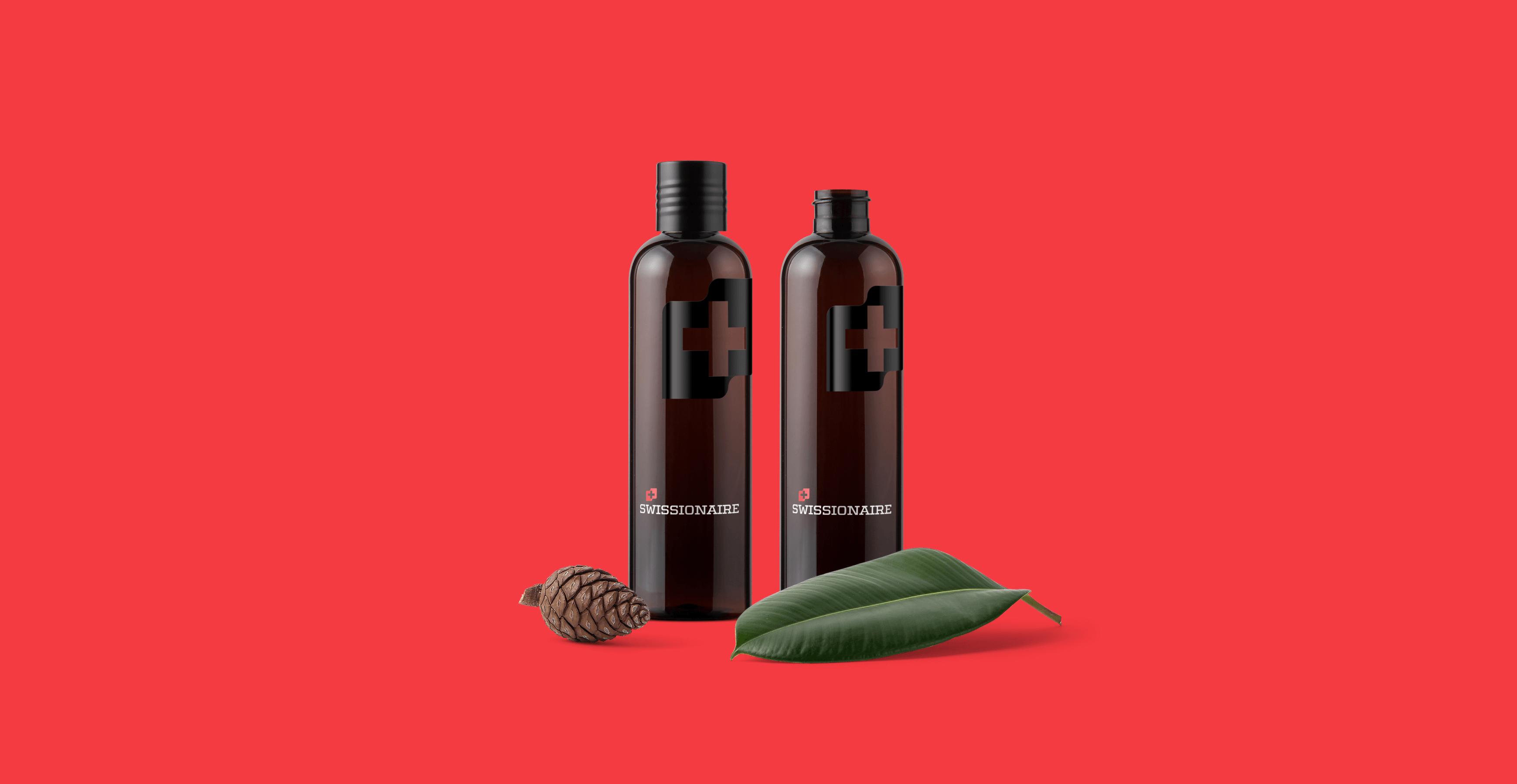 Pohled na dvě flašky s kosmetikou. V popředí leží šiška a zelený list.