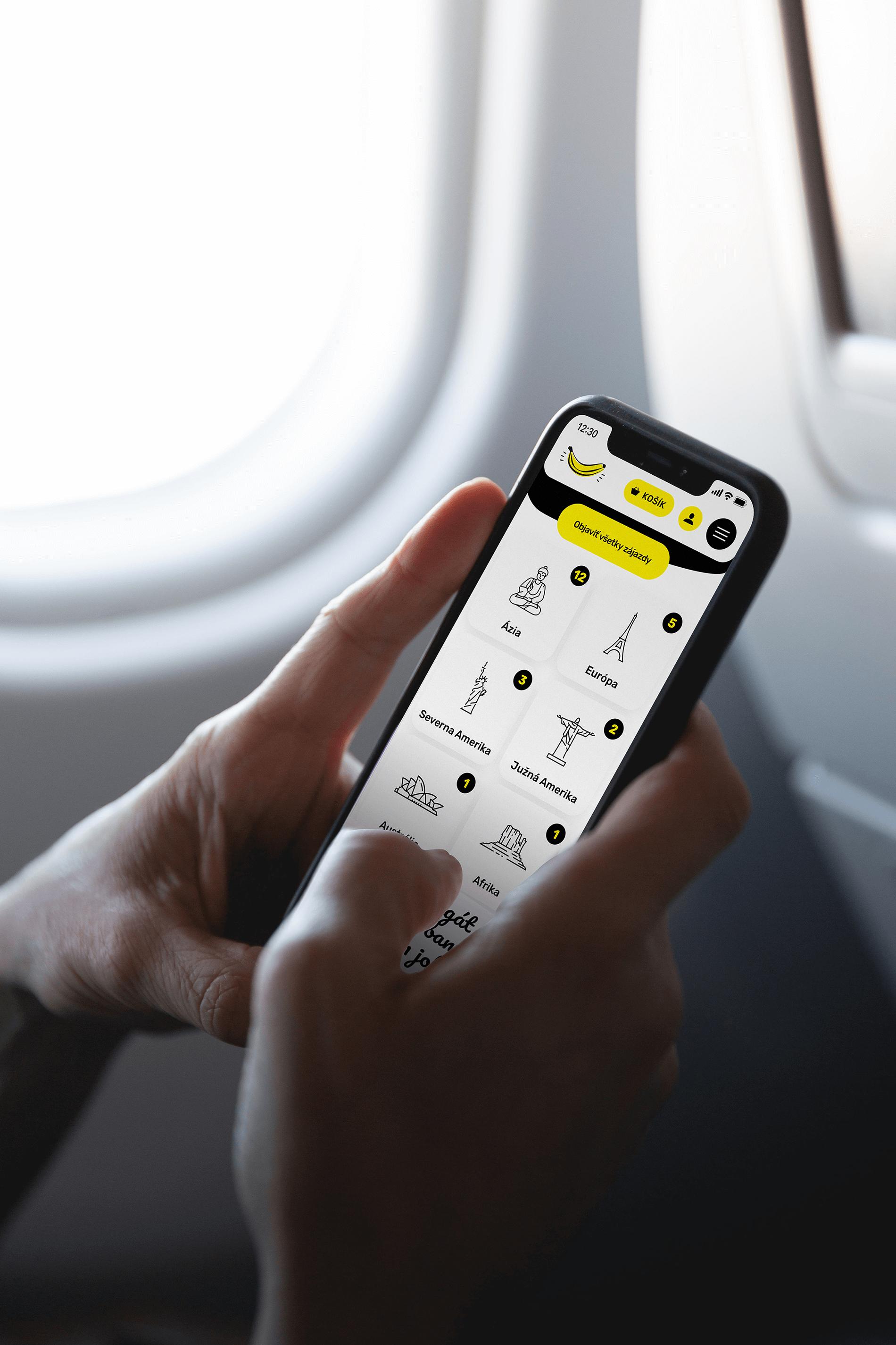 Pohled na ruce držící mobilní telefon při letu v letadle.