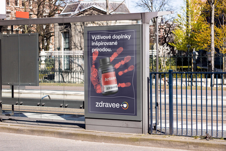Pohled na autobusovou zastávku, na které je citylight s plakátem s výživovými doplňky.