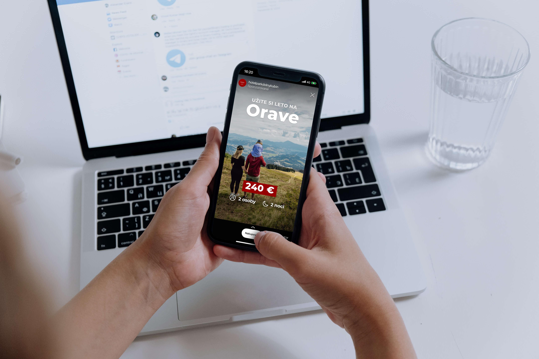 Pohled z první osoby na ruce, které drží mobilní telefon. Na displeji je sponzorovaný příběh. V pozadí počítač značky Apple.