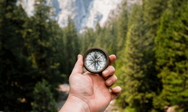 Ruka držící historický kompas. V pozadí je les a hory.