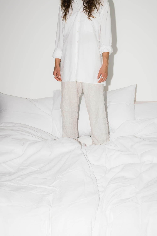 Frau in einem weissen Kleid steht auf einem Bett