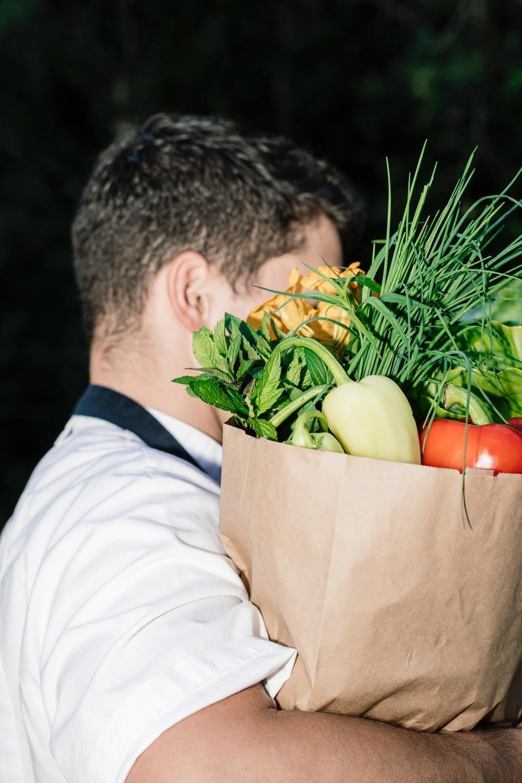 Küchenchef mit einer Tüte voller frischem Gemüse