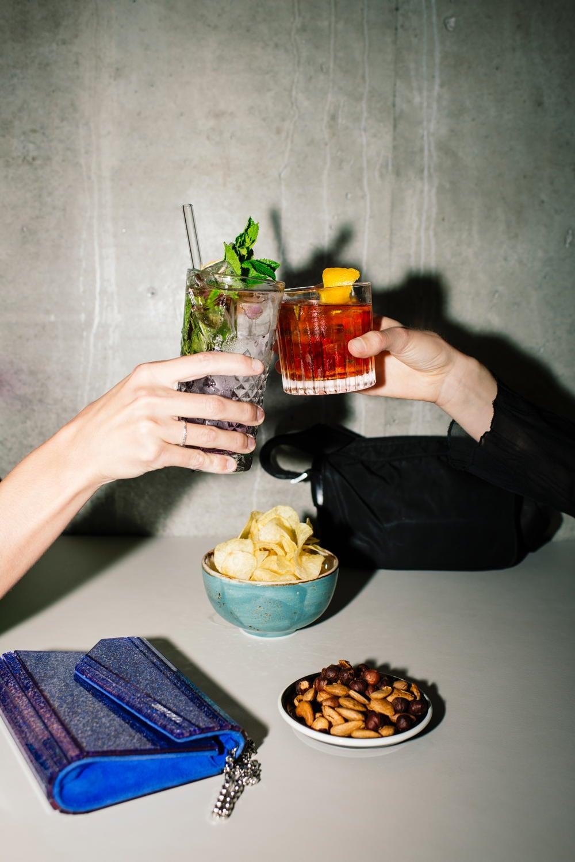 Zwei Personen stossen mit ihren Cocktails an
