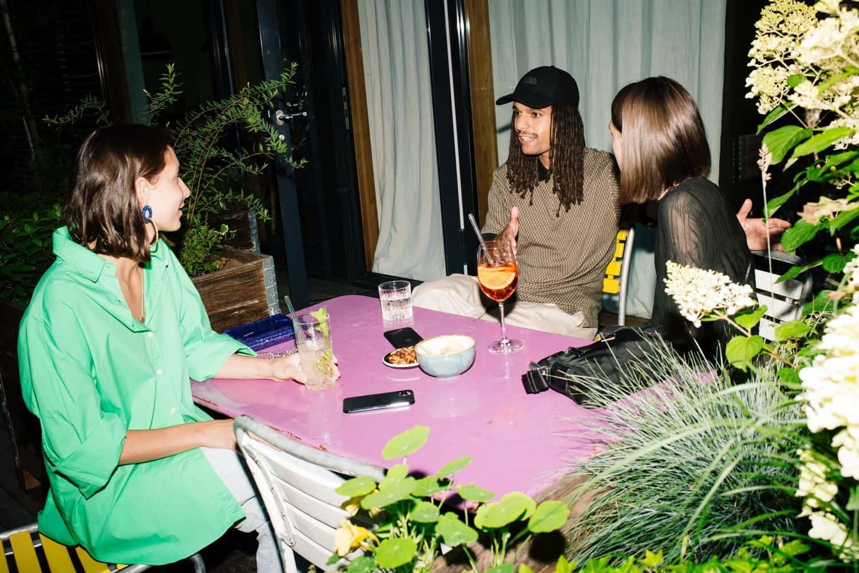 Zwei Frauen und ein Mann sitzen auf an einem Tisch im Aussenbereich des Hotels
