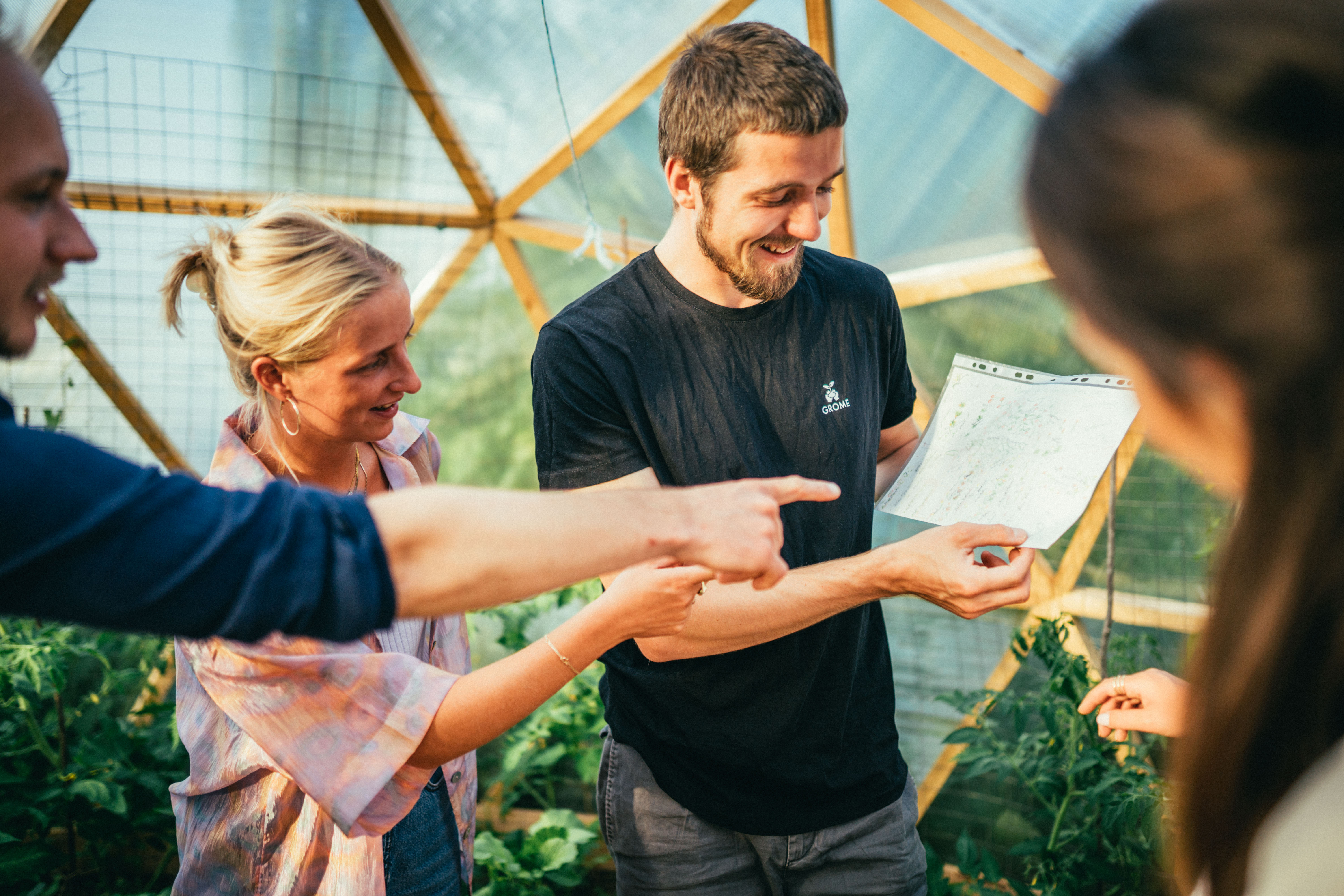 Hanno is in a greenhouse teaching to three workshoppers. Hanno is similing and everybody indicate the small blackboard