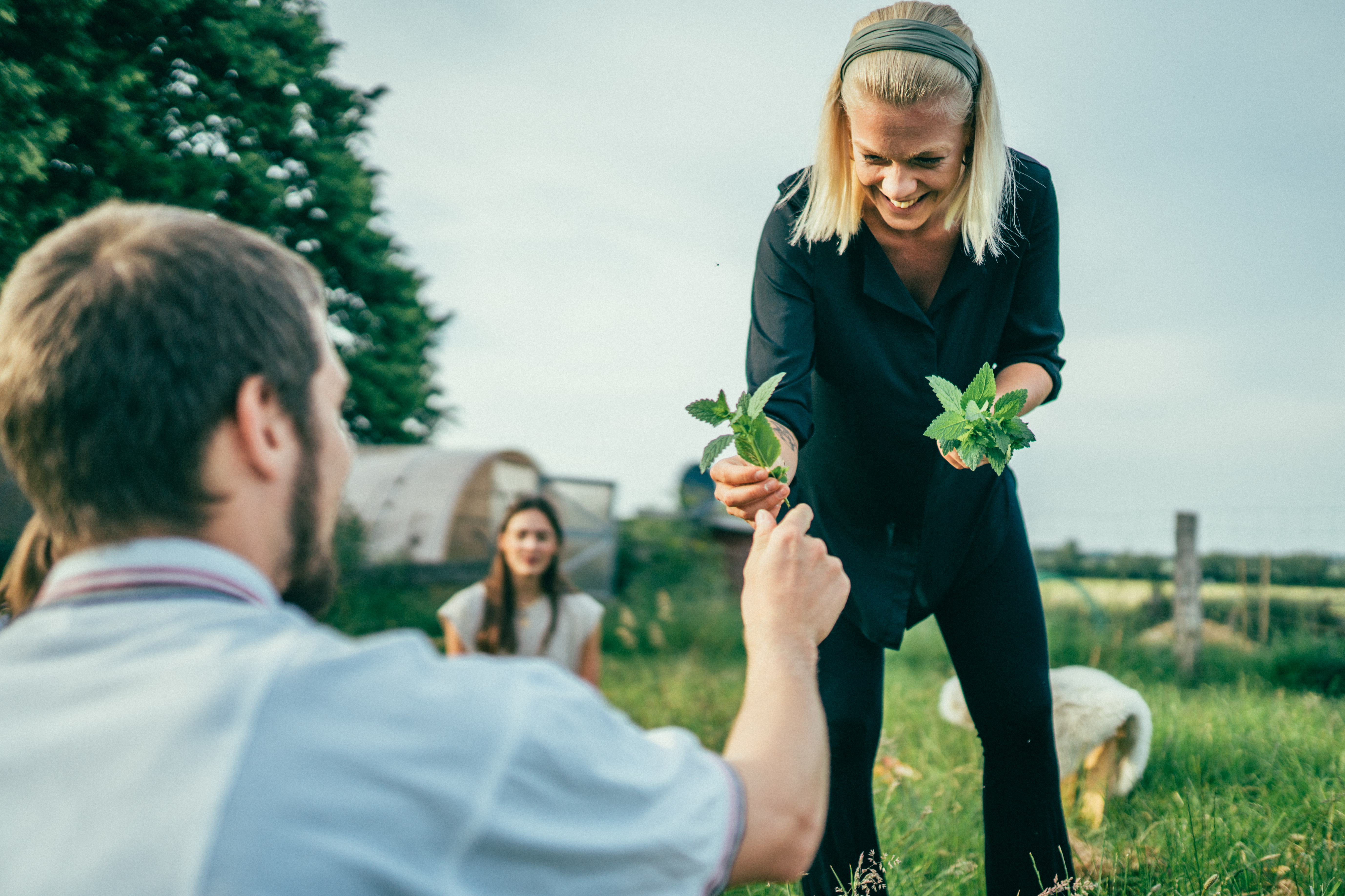 Lisa is handing a small vase with a plant in ti to Hanno. Both are outside in the sunny garden during an event. There's people in the background.