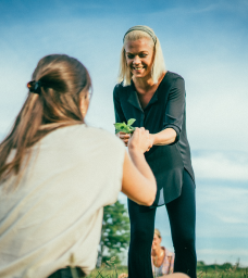 Lisa smiling and handing a plant to a girl during a workshop