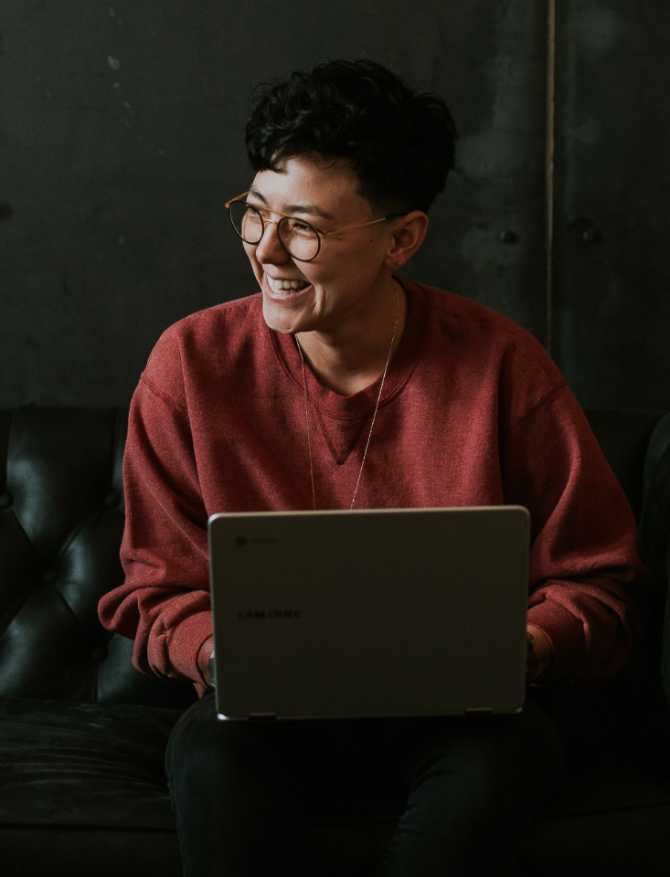 woman behind the laptop, smiling, looking off to the side