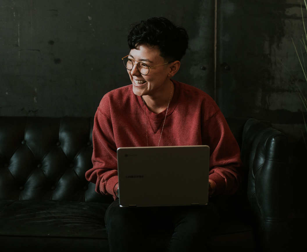 woman behind the laptop, smiling looking off to the side