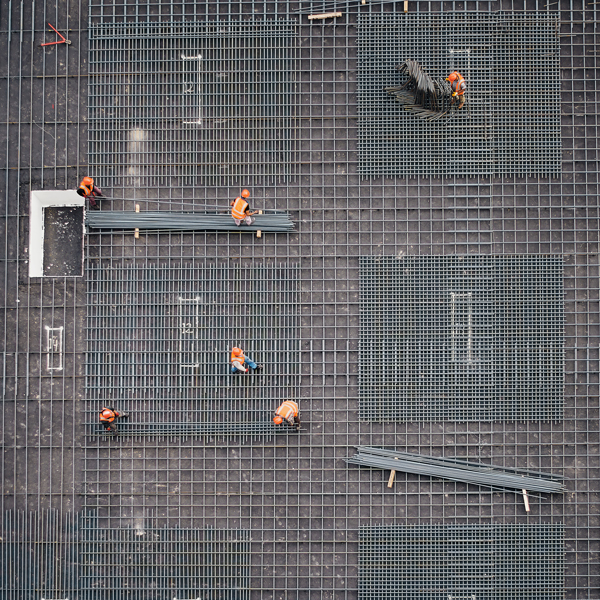 Zoomed out image of construction workers on rooftop construction site