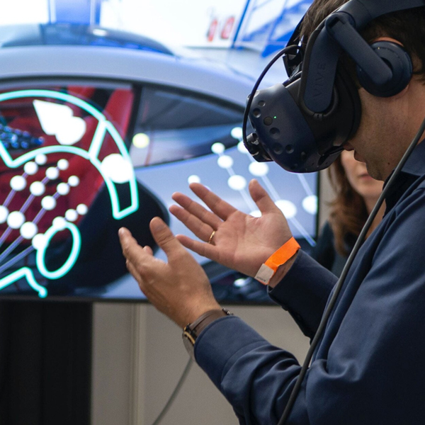 Man wearing AR/VR glasses in front of cars