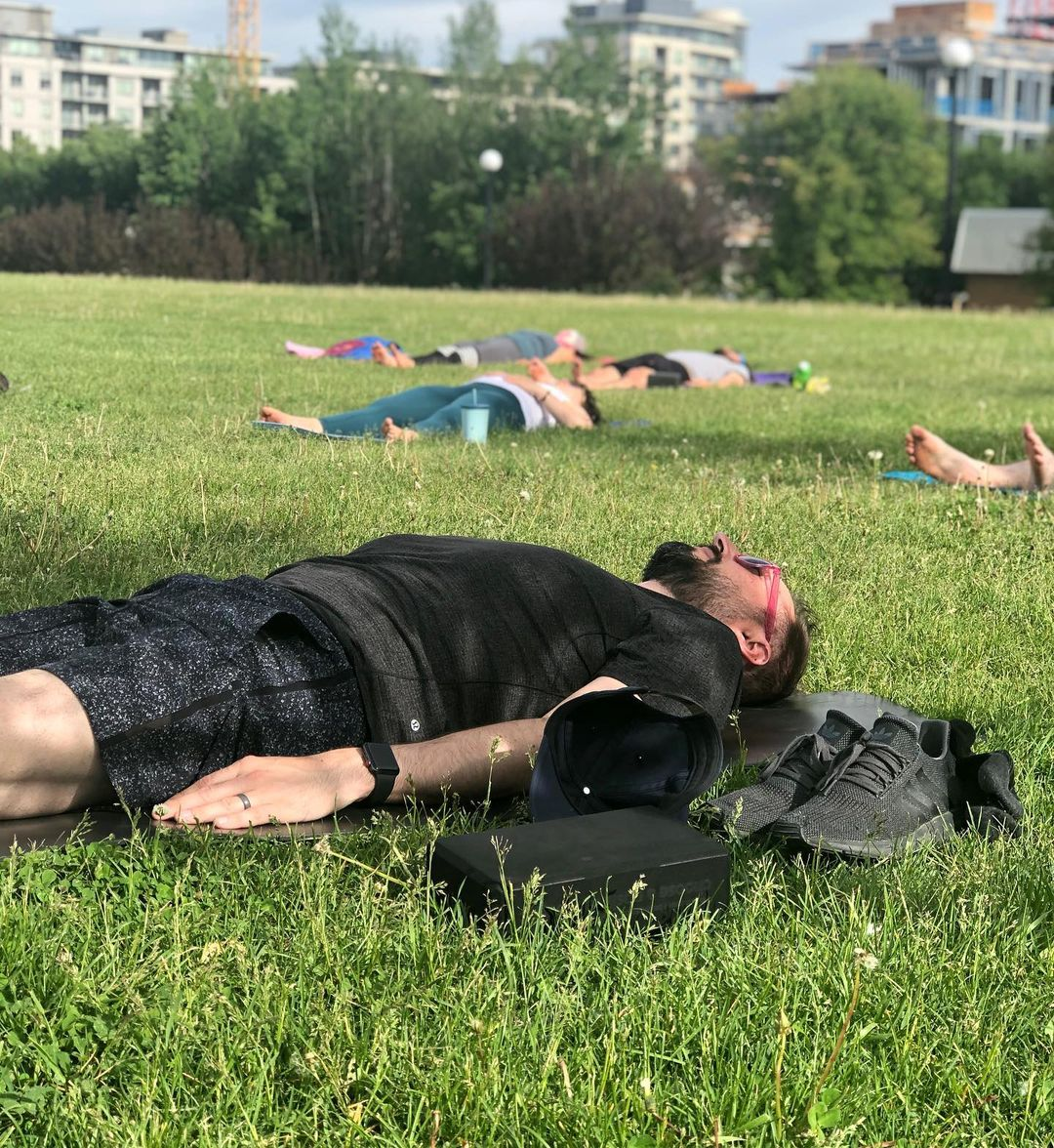 People laying in the grass doing yoga