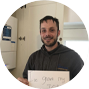 A tradesperson holding a sign that reads I'm winning more work