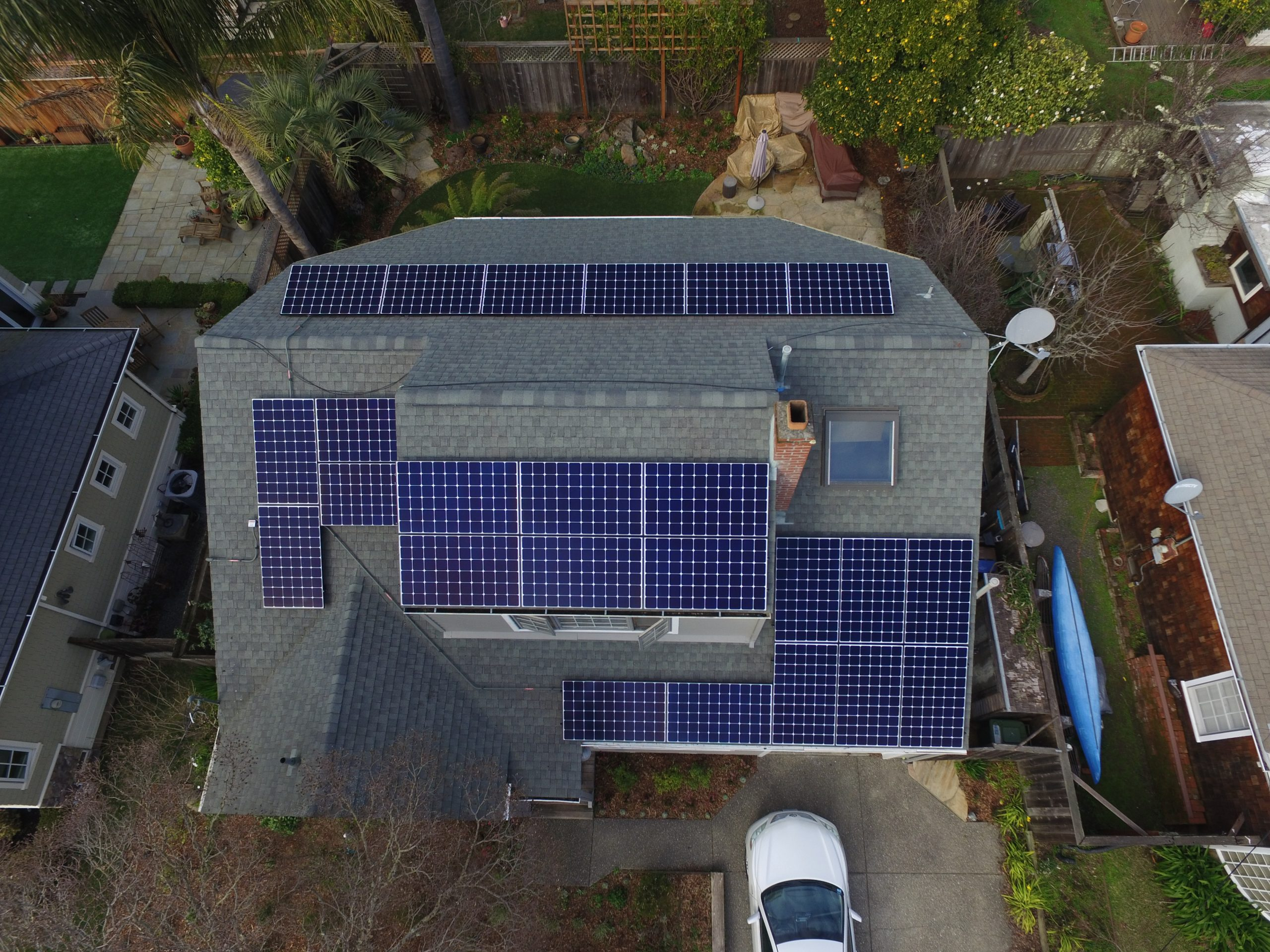 Residential rooftop solar installation from above showing display of different solar arrays