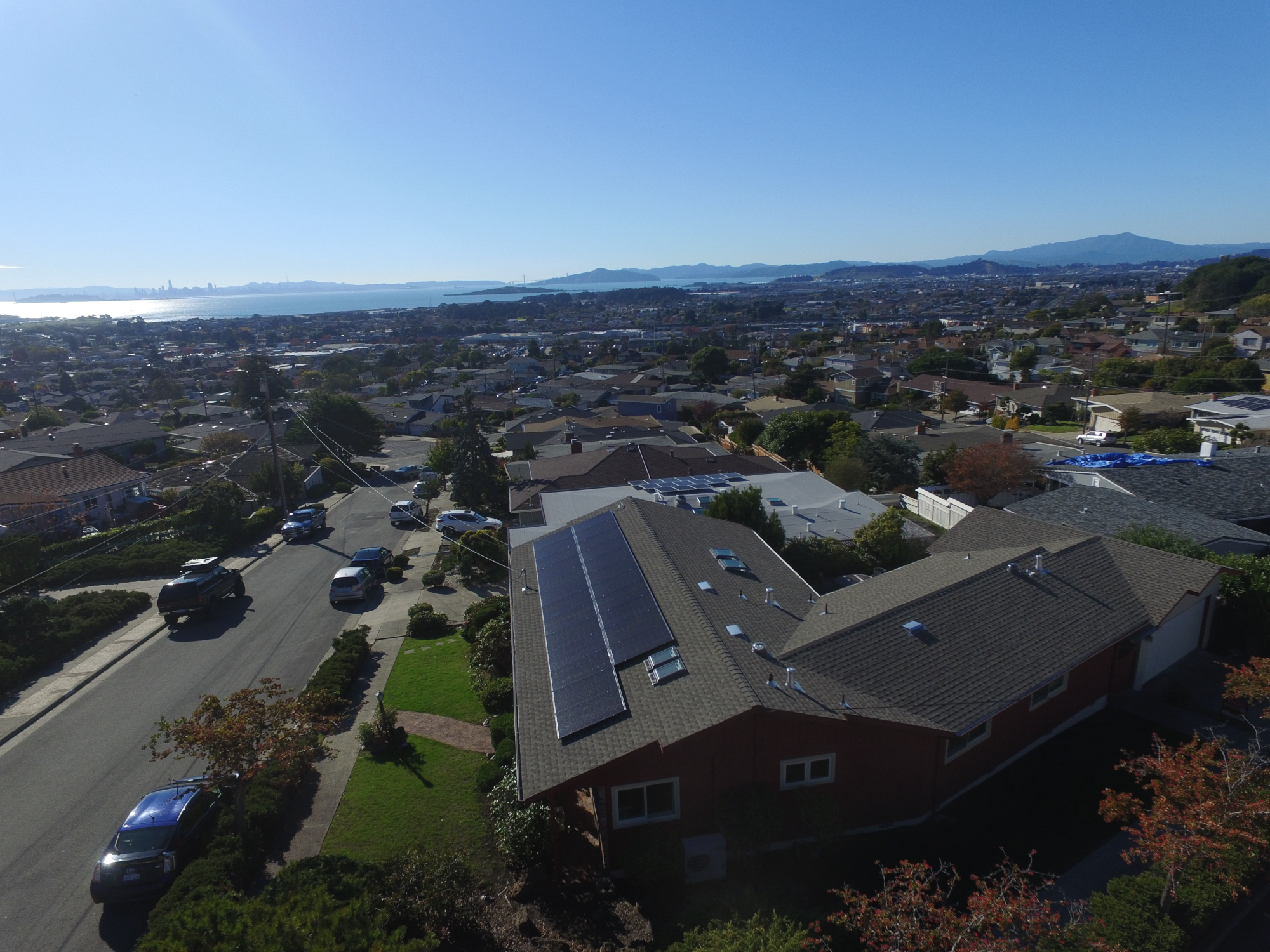 Aerial view of a residential rooftop solar installation looking out across the East Bay to the water