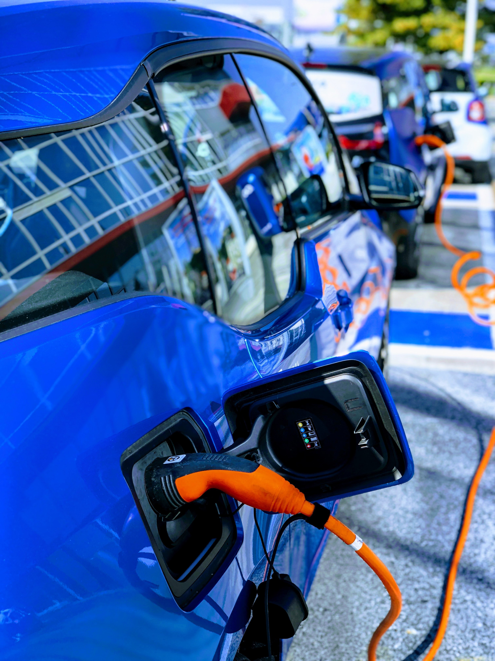 Close up of two blue electric vehicles being charged with an orange cable