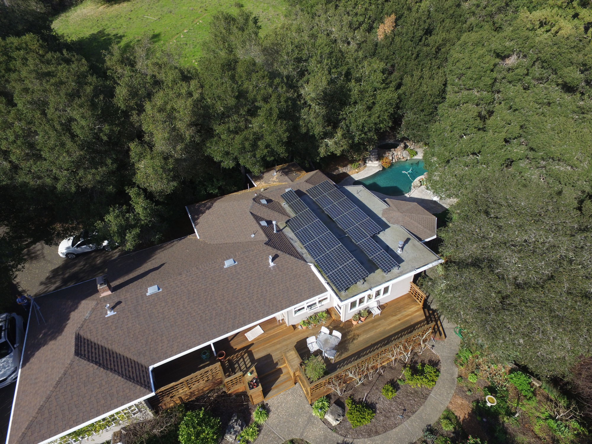 Aerial rooftop solar showing two tilted panel arrays facing south on a home surrounded by lush green trees