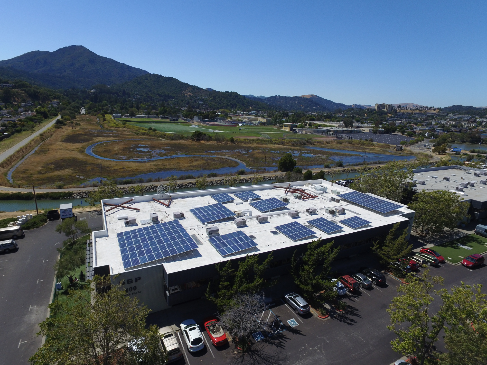 Aerial view of commercial solar installation at Tamal Plaza offices in Corte Madera, Marin County, CA. With Mount Tamalpais in the background