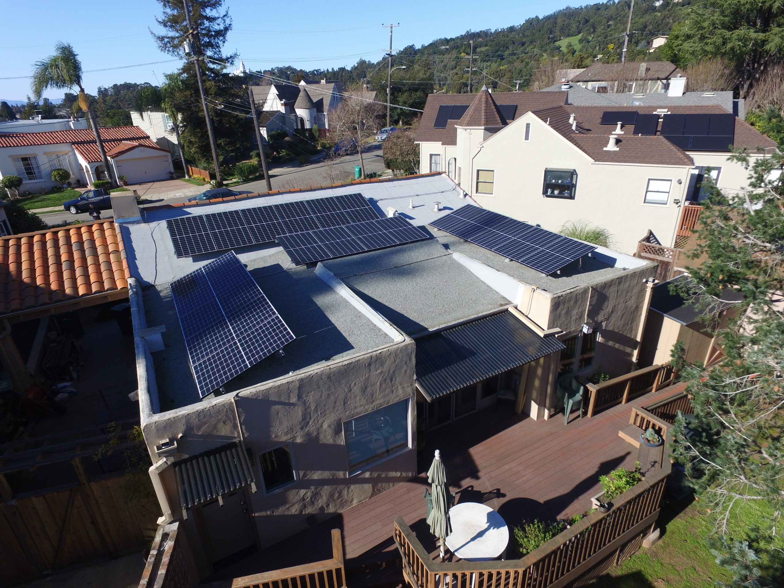 Residential solar installation showing four tilted panel arrays on an Oakland home