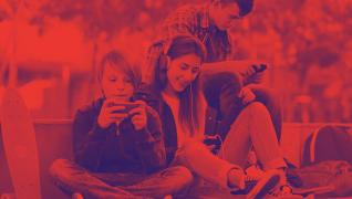 Trois adolescents dans une cour d'école sur leur cellulaire.