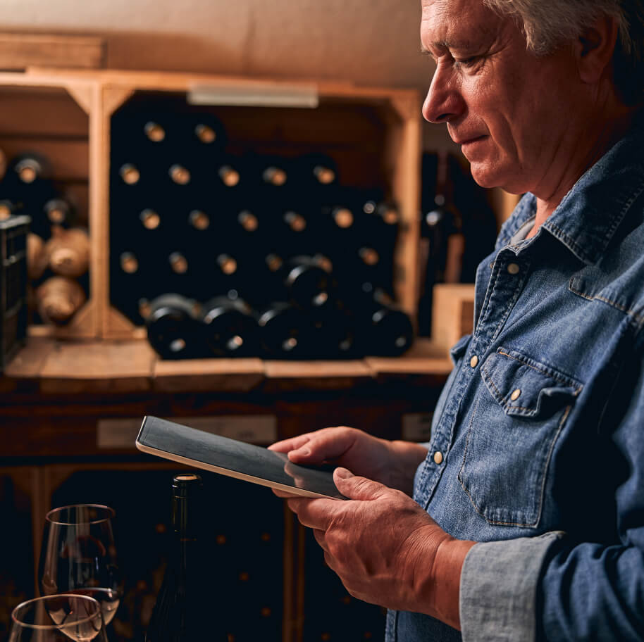 Winemaker at winery with bottles in the background visiting a website on his iPad.