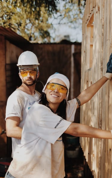 Man and woman with construction hats building a fence.