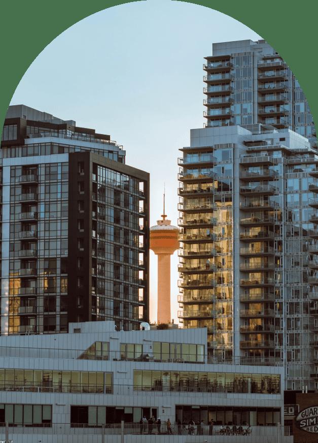Calgary tower peeking between two large apartment buildings in Calgary