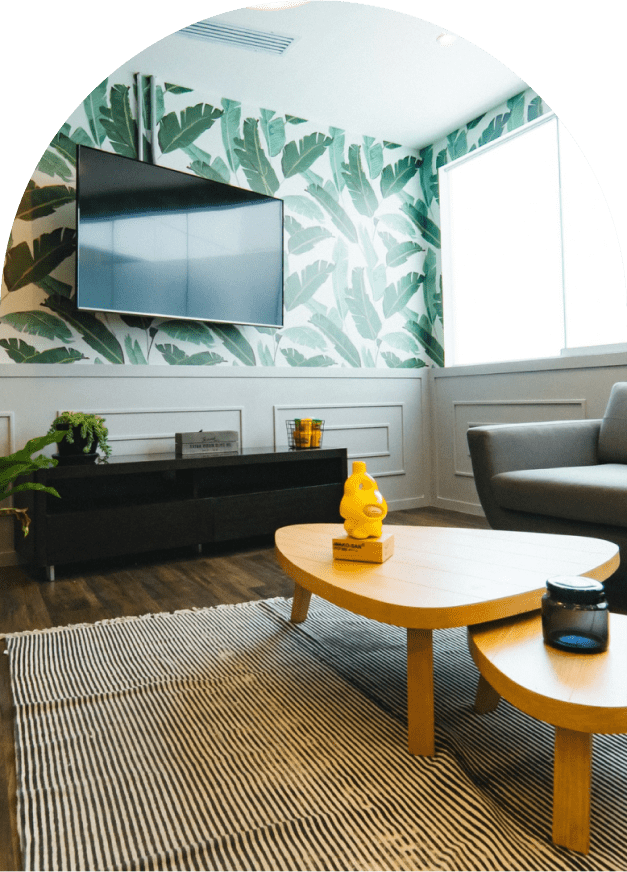 charming living room with plant wallpaper, tv mounted on wall and small wooden tables