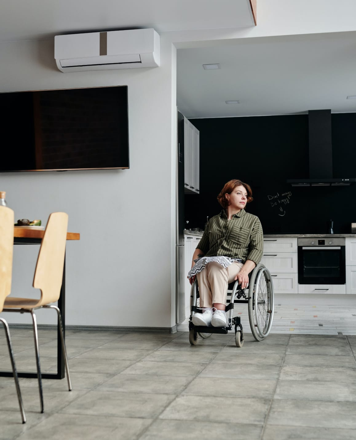 Women in wheelchair at the entrance to her kitchen