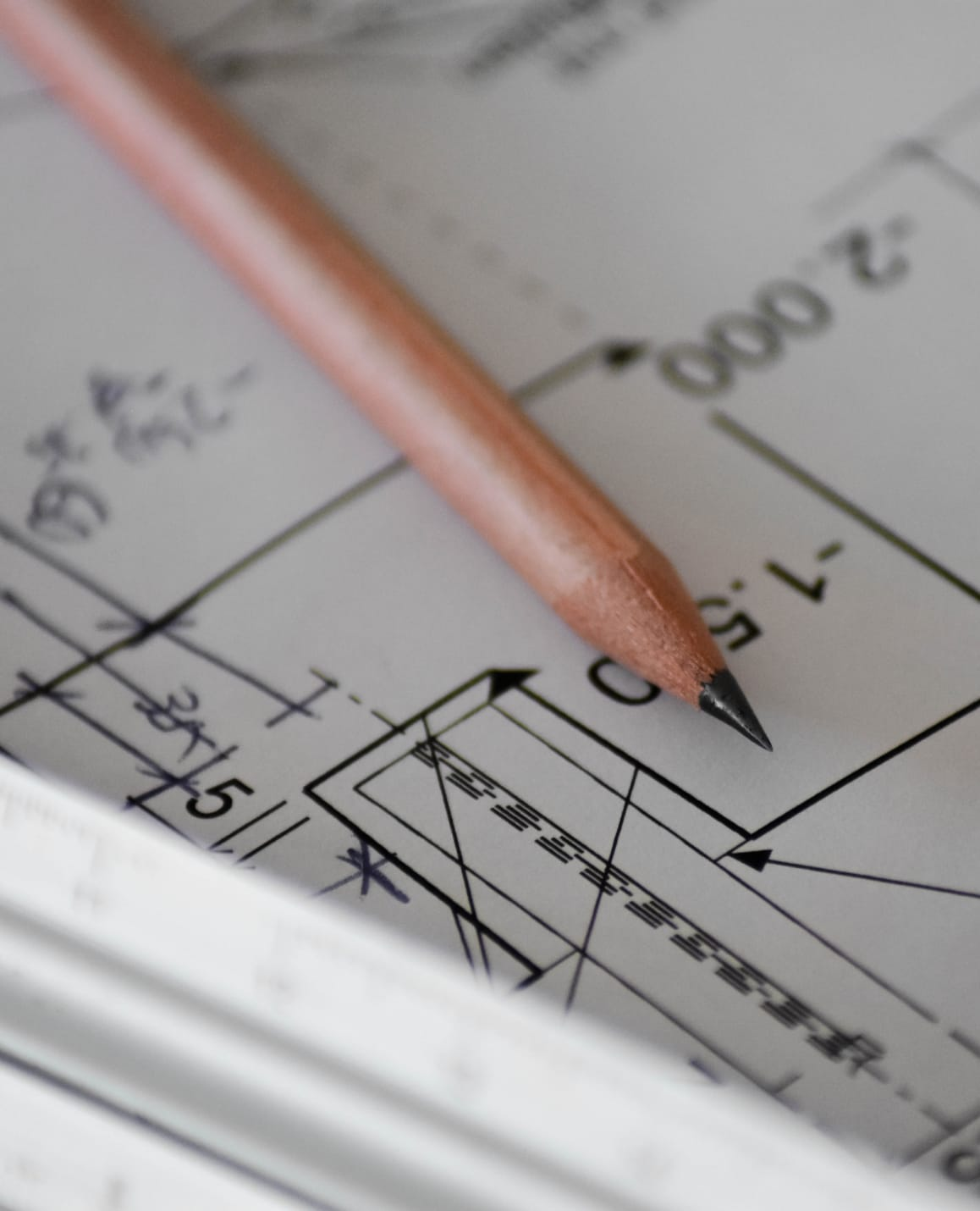 Pencil laying on top of blueprint house drawings