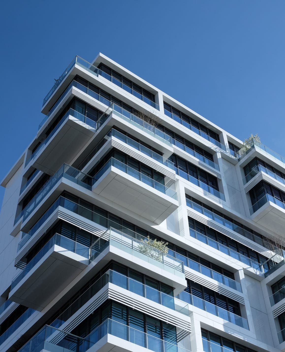 Looking up at a white, modern apartment building