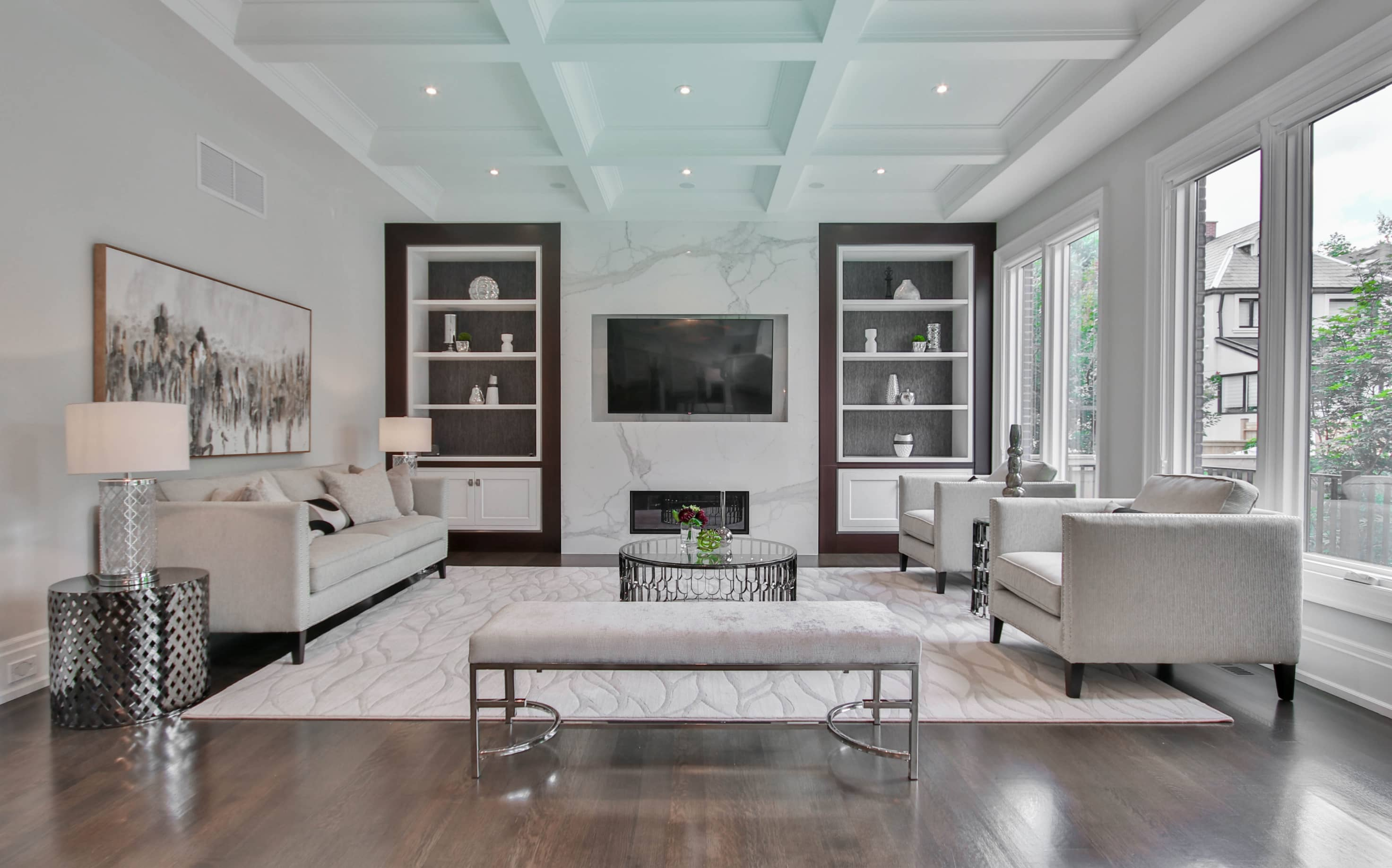 Large white living room with couches, coffee table and bookshelves
