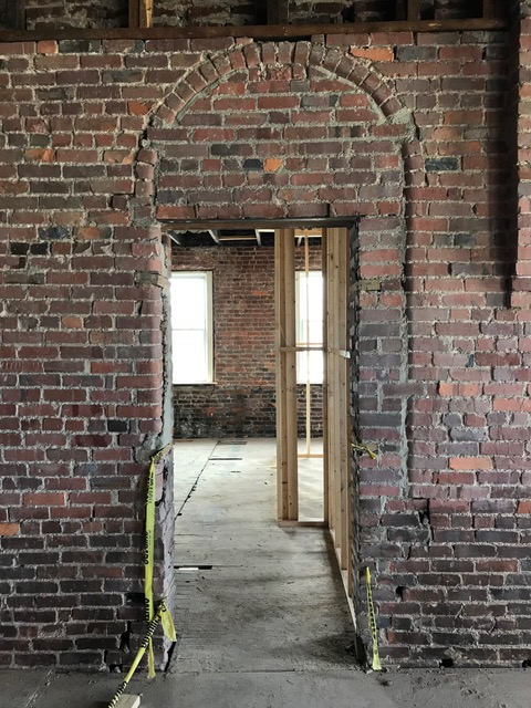 Arched window, now entry to restrooms
