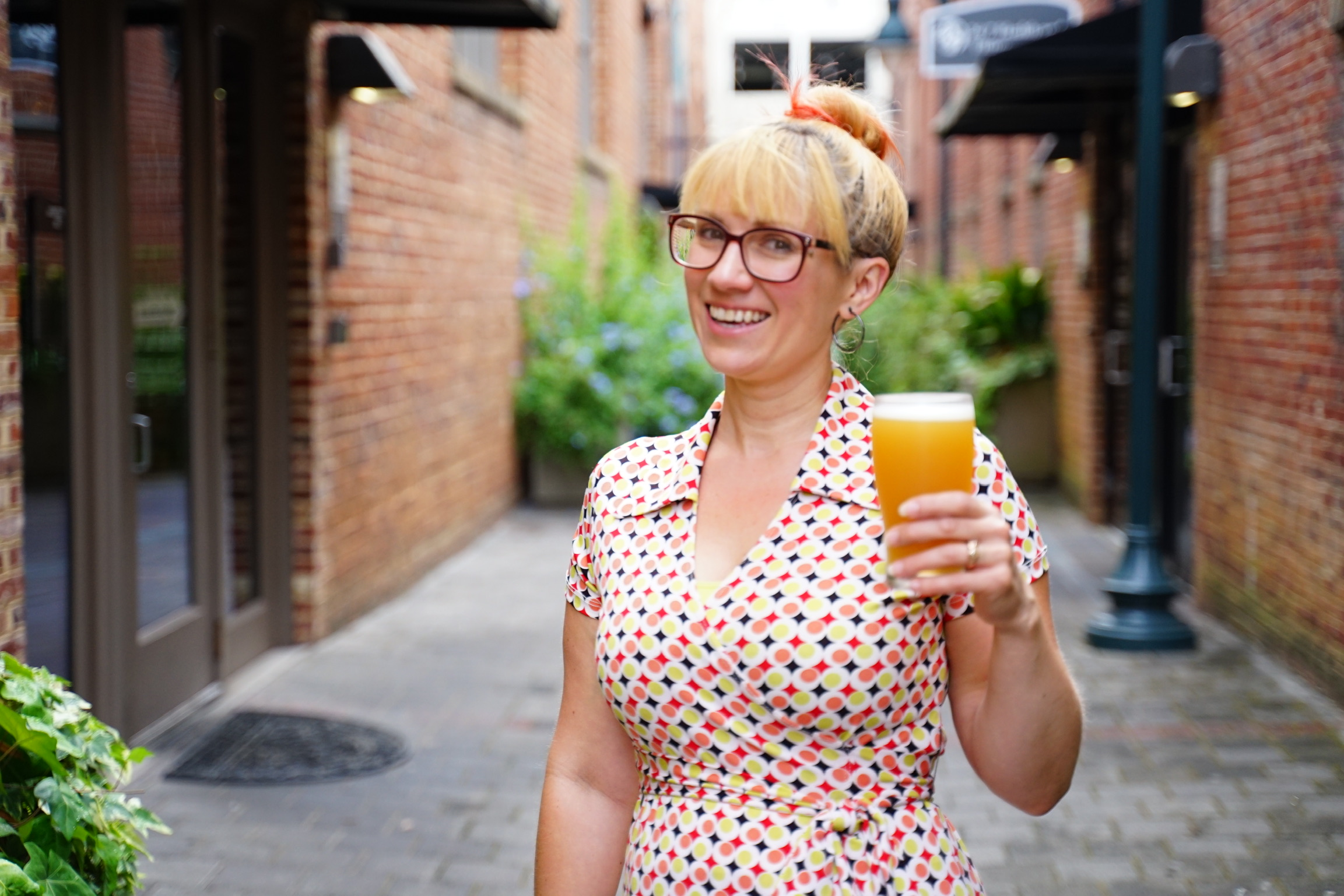 An image of a woman with glasses smiling and holding a pint of beer.