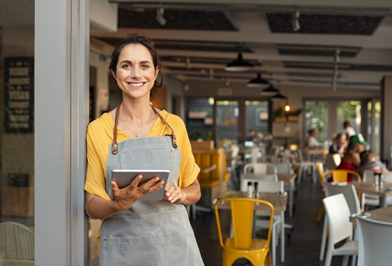 Woman wearing an apron and holding a tablet