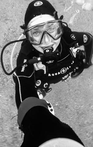A female scuba diver taking a selfie underwater.