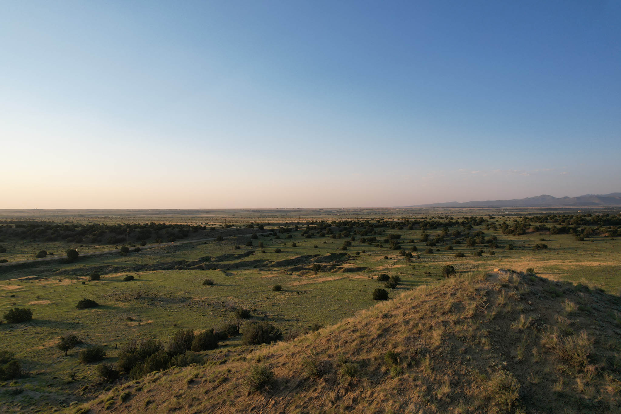 Sun rises in a cloudless sky over green prairie and mountainst
