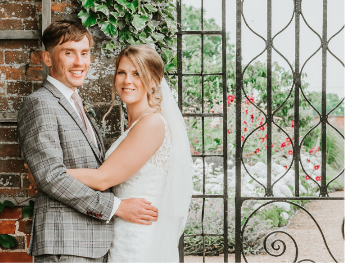 A newly wed couple standing in front of the elegant gate of their wedding venue. Gemma Randall Photography ©