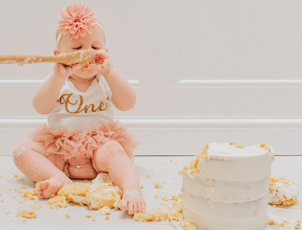 A baby girl cheekily eating her first birthday cake during her cake smash photoshoot. Gemma Randall Photography ©