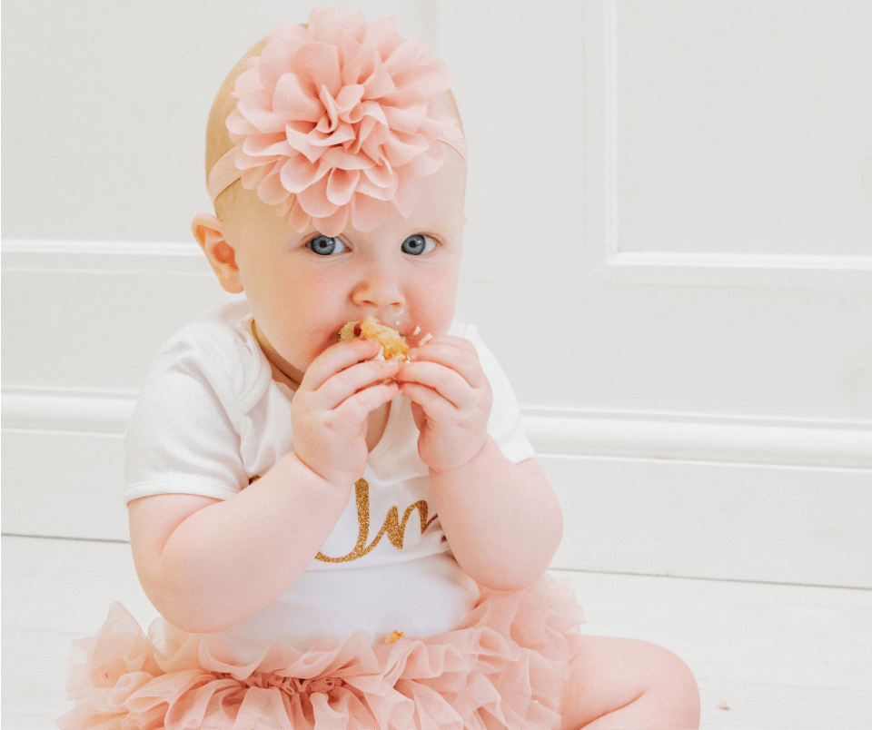 A baby girl munching down on her first birthday cake during her cake smash photoshoot. Gemma Randall Photography ©