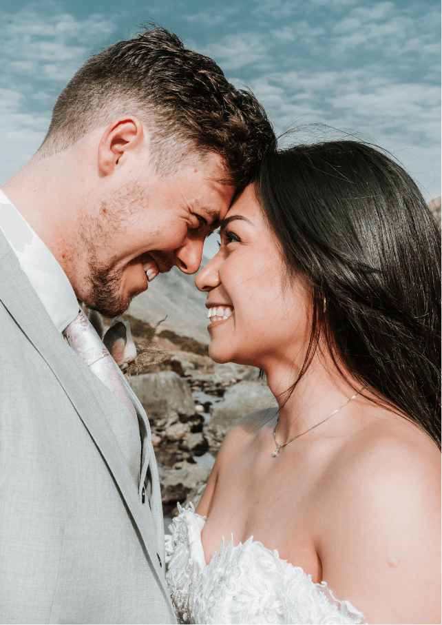 A photo of a newly wed couple smiling into each other's faces with a gorgeous blue sky overhead. Gemma Randall Photography ©