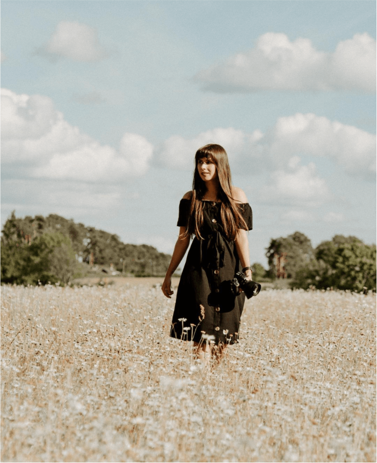 A photo of Buckinghamshire based wedding and studio photographer, Gemma Randall standing in the middle of a golden field with a camera.