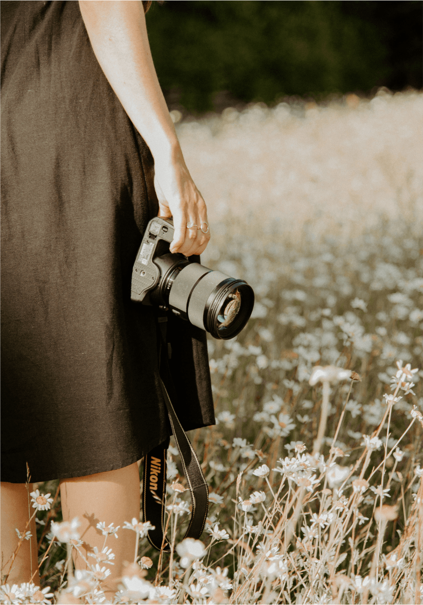 A photo of Gemma holding her camera in a sunny field of daisies