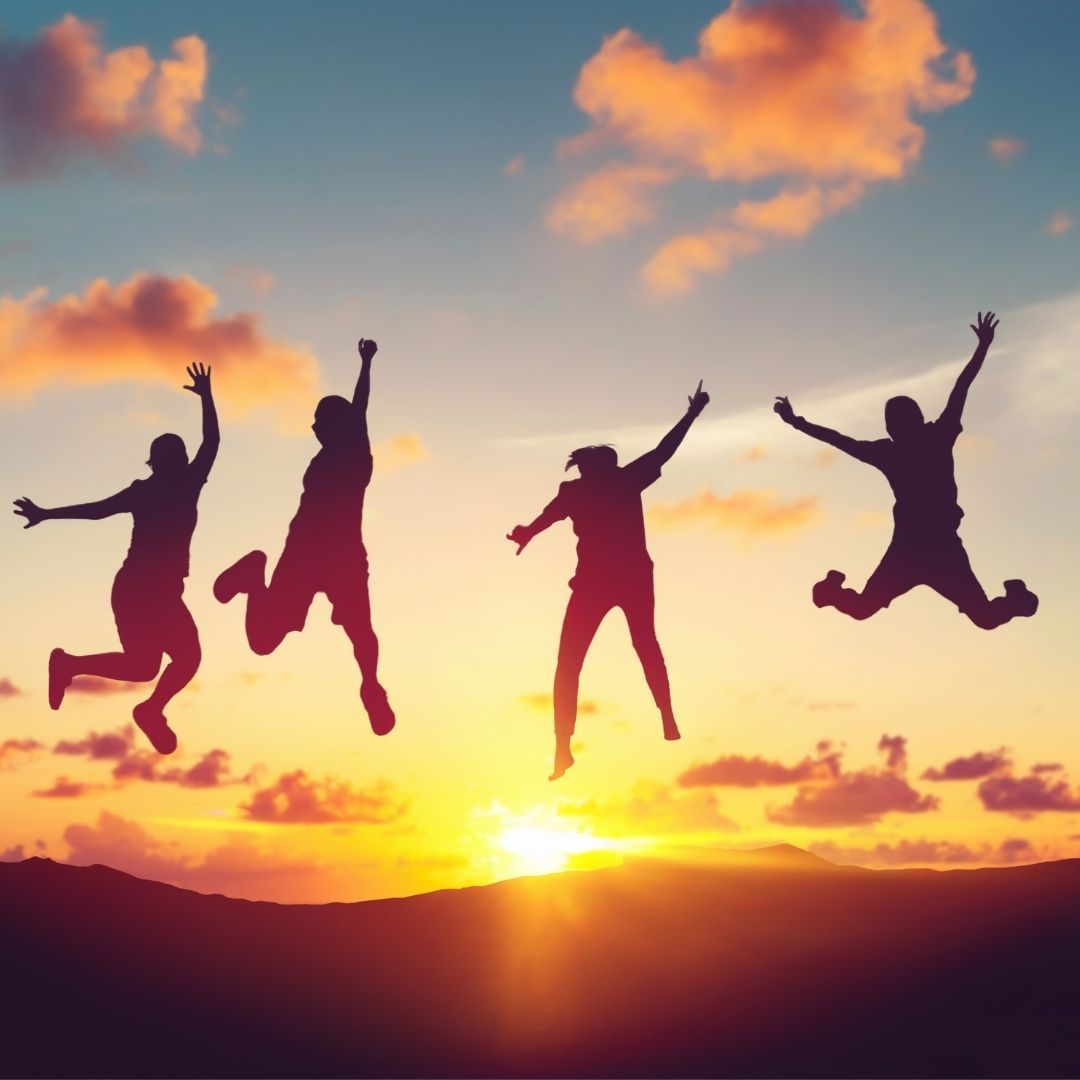 Silhouettes of enthusiastic people jumping in front of a sunset.