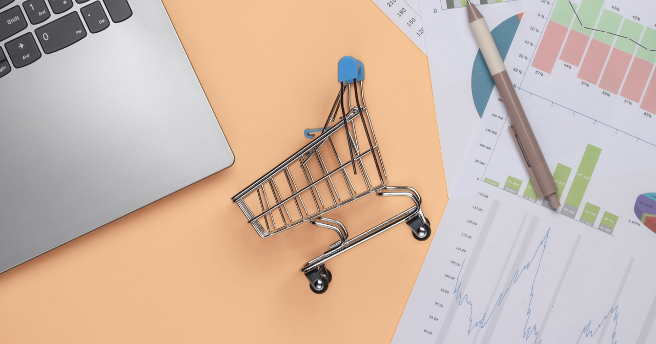 a shopping cart toy flat layed between a computer and a noting pad.